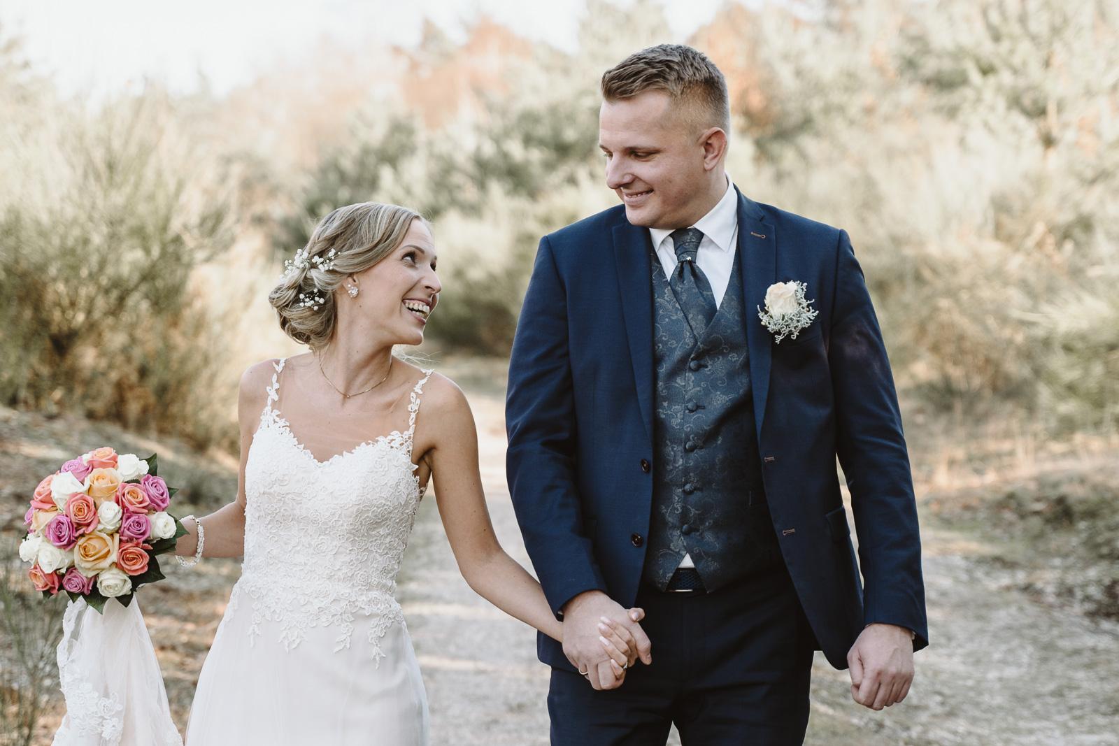 Hochzeitsfotografie - Ehepaar geht nach der Trauung froh gelaunt spazieren