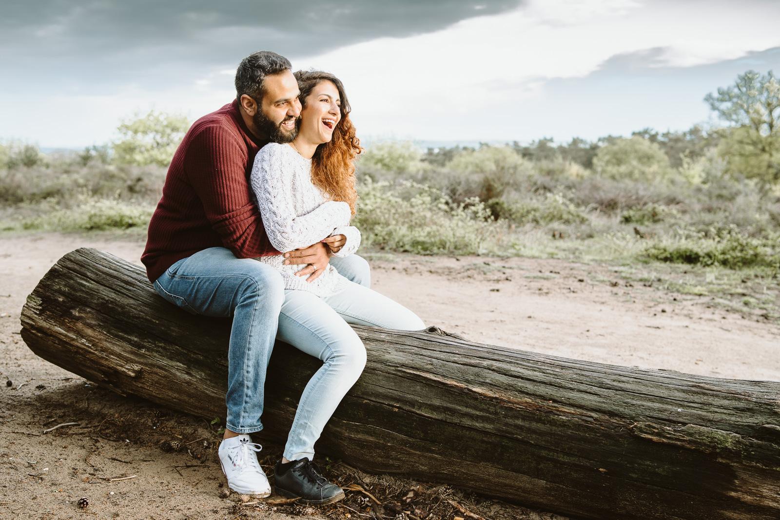 Paarfotografie-Mann und Frau sitzen auf Baumstamm